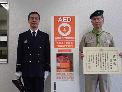 立川消防矢ヶ崎副署長(左)から表彰状を受け取る溝呂木さん(右)